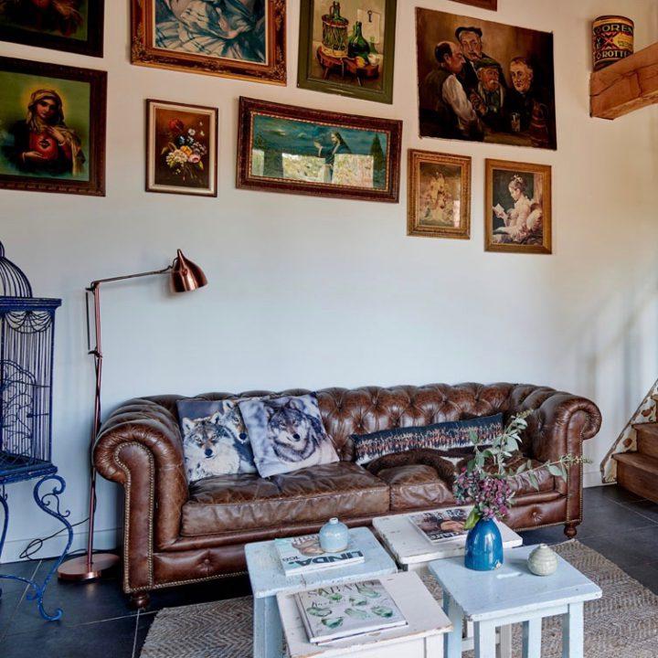 Zithoek met bruine leren Chesterfield en losse salontafels, diverse schilderijen erboven