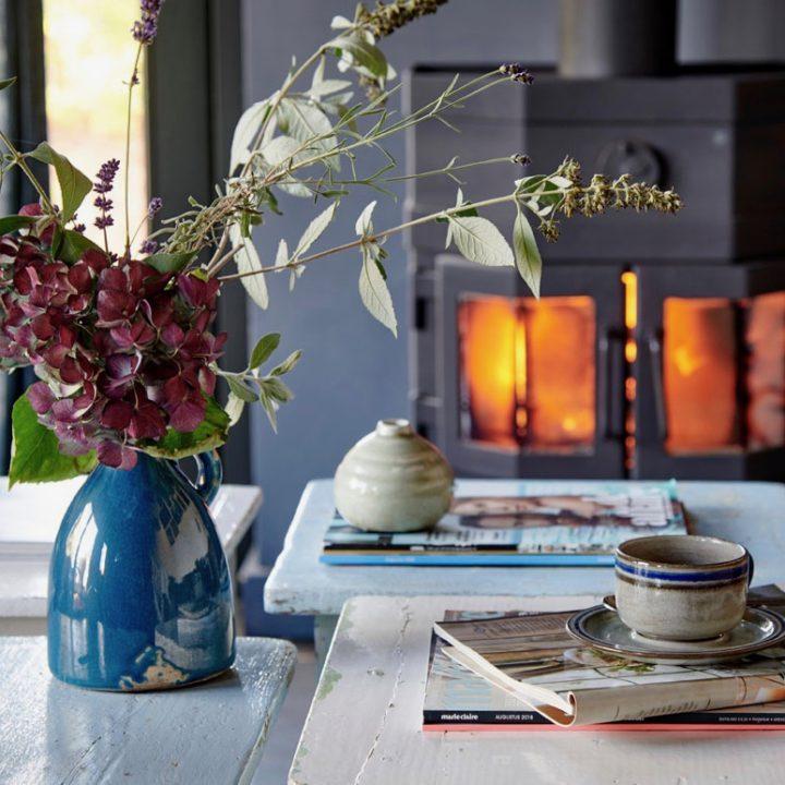 Tafeltjes met tijdschriften, bloemen, koffiekopje voor brandende houtkachel
