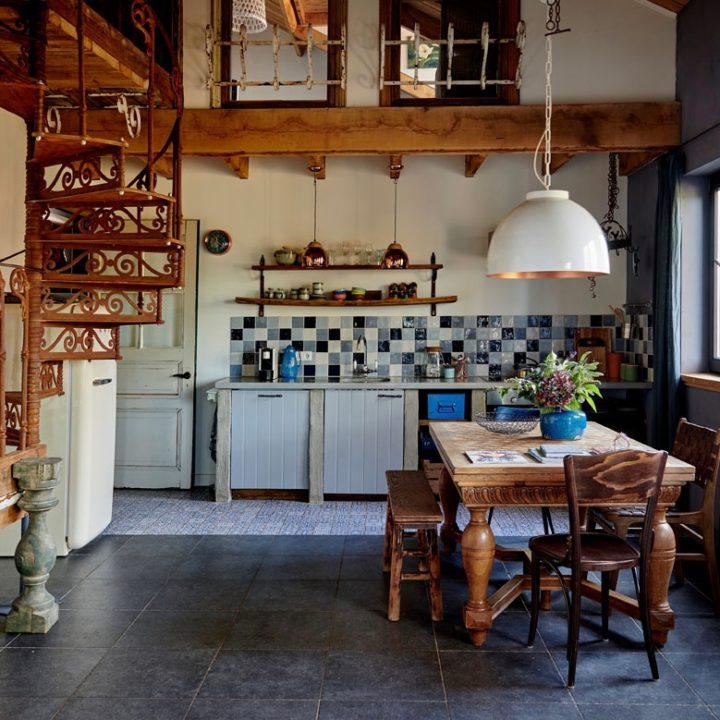 Appartement met houten tafel, gietijzeren trap en keukenblok met blauwe tegels