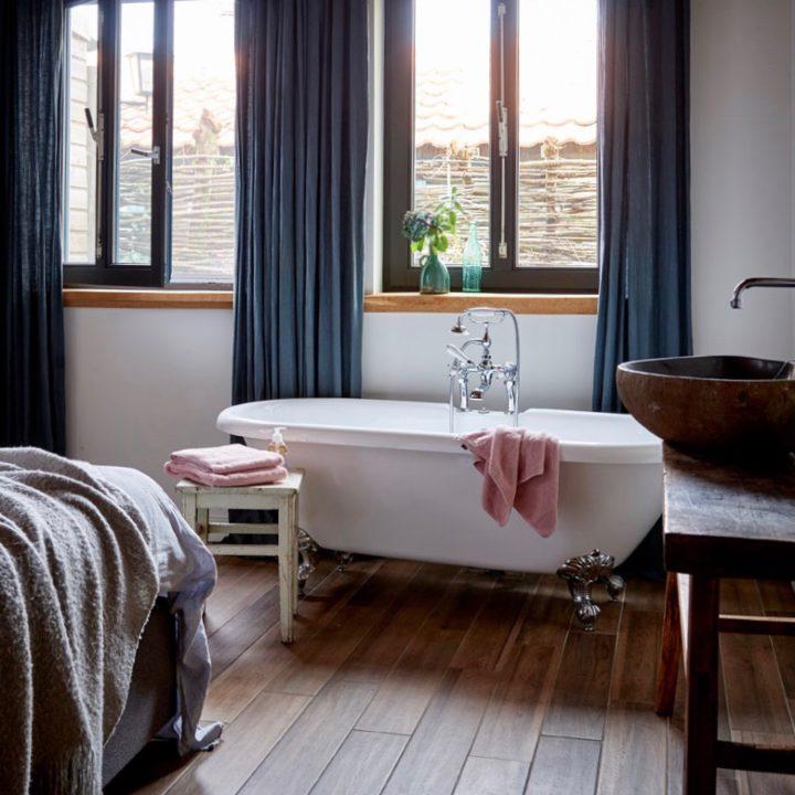 Bad op pootjes, roze handdoeken en ramen met blauwe gordijnen