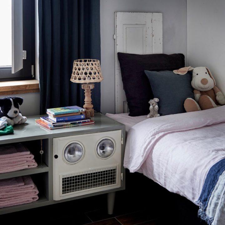 Bed met kussens en knuffels, nachtkastje met stapel kinderboeken en nachtlampje