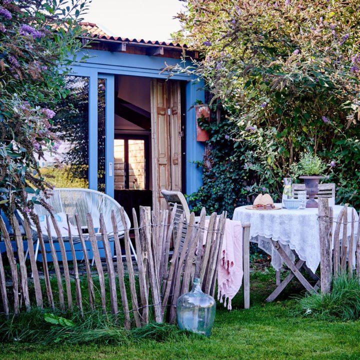 Tweepersoons appartement met tafeltje en bankje ervoor in het gras