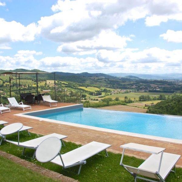 Zwembad met uitzicht over heuvels, witte ligstoelen bij het water