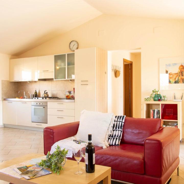 Witte moderne keuken met rode fauteuil in zithoek in een vakantiehuis