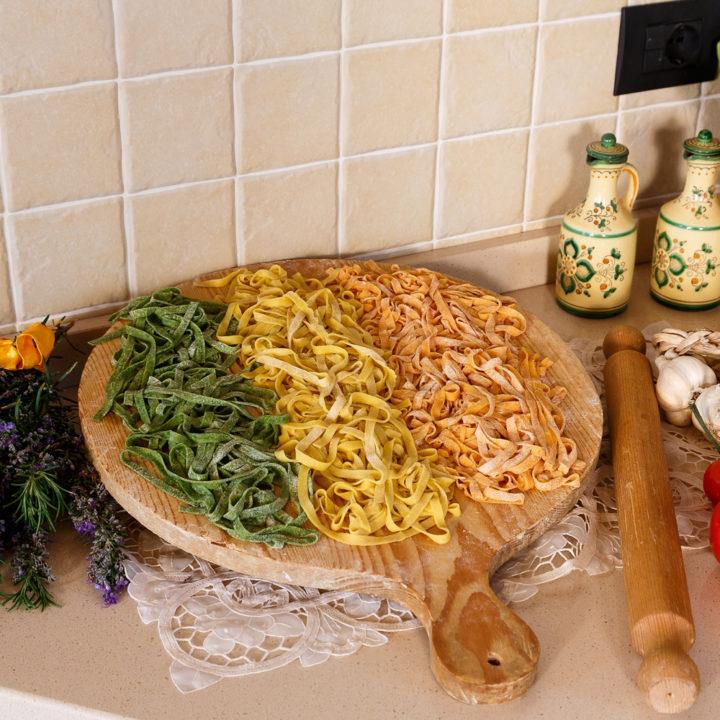 Houten plank op aanrecht met drie soorten pasta