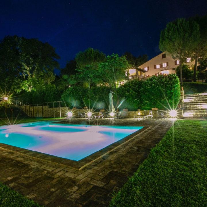 Zwembad by night, verlicht met op de achtergrond een vakantiehuis
