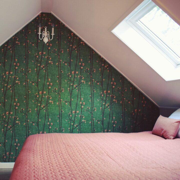 Slaapkamer met roze sprei en groen bloemenbehang