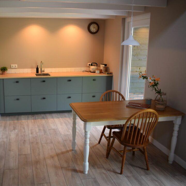 Grijze keuken en houten keukentafel