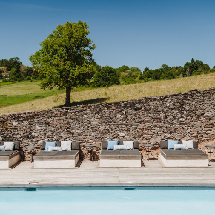 Zwembad met loungebanken met bruine, witte en blauwe kussens