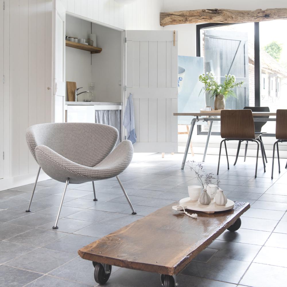 Een licht interieur met stoere houten salontafel en licht grijs fauteuiltje