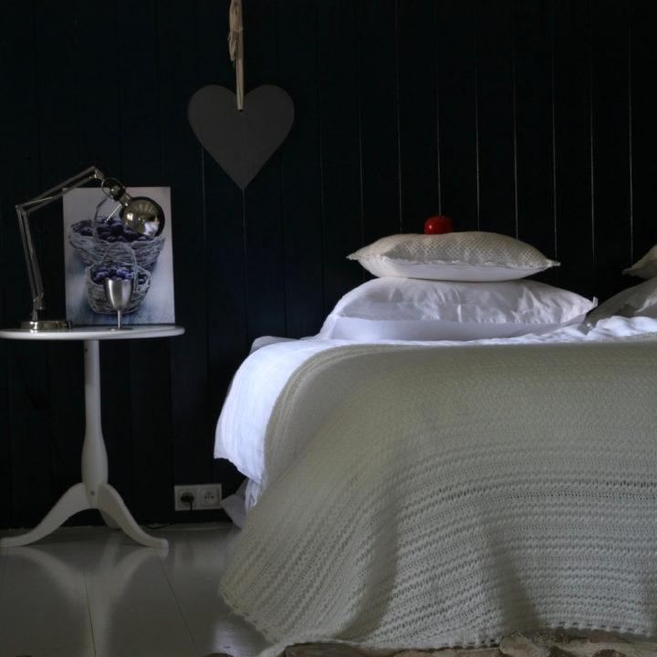 Opgemaakt bed met witte sprei tegen zwarte achterwand
