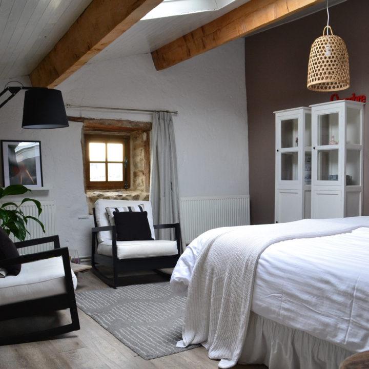Een gastenkamer, met stoeren balken, witte kast, wit bed en twee fauteuils, landelijke stijl