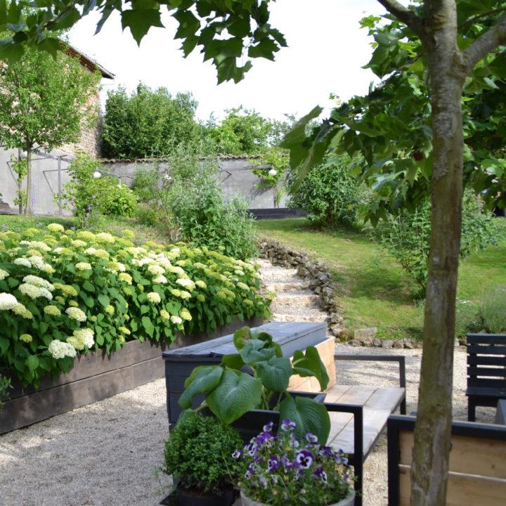 Tuin met paadje door het gras en zittje onder bomen