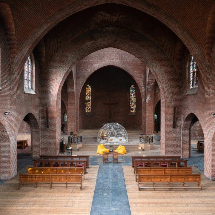 Kerk met transparante koepel met bed erin