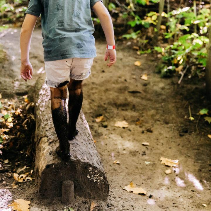Jongetje in korte broek, op blote voeten, volledig onder de modder in het bos