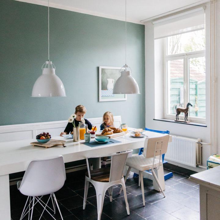 twee kinderen aan een lange witte tafel, in een licht en modern vakantiehuis