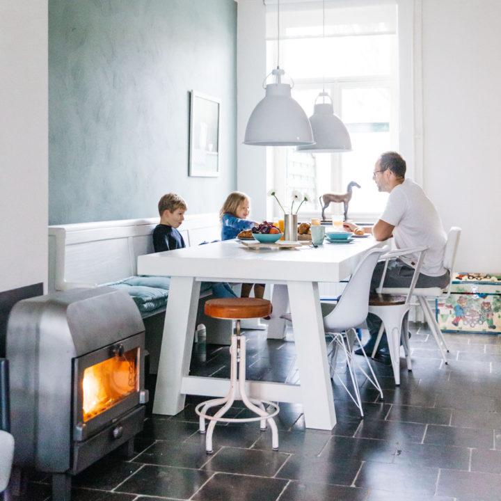 Brandende kachel naast een witte eettafel met verschillende stoelen waar een gezin zit te ontbijten.