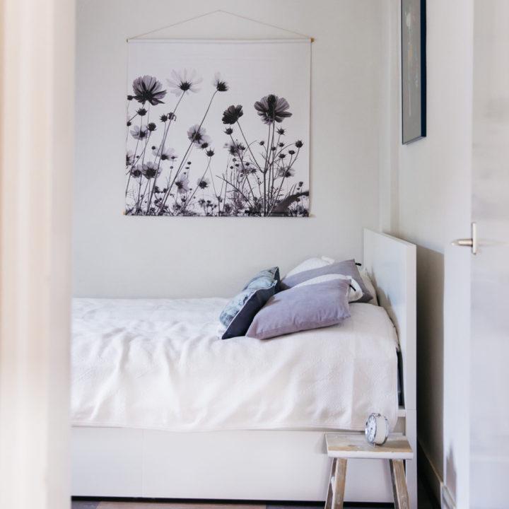 Witte slaapkamer met wit opgemaakt bed en lichte kussen.