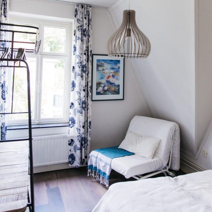 Slaapkamer met een tweepersoons bed, een zwart kledingrek en een zitbank die uitgeklapt kan worden tot bed