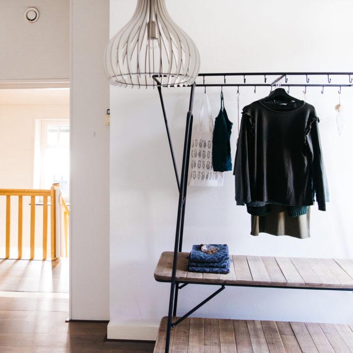 Overloop met moderne lamp en kledingrek met zwarte kleding er aan