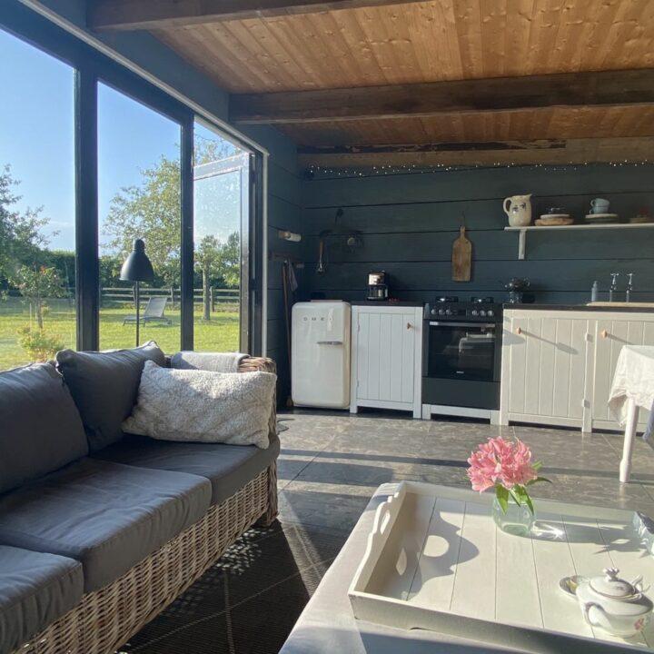Midden in de boomgaard staat de tuinkamer, met een buitenkeuken, houtkachel en loungebanken.