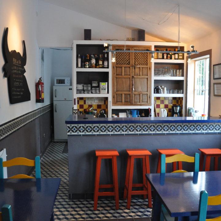 Bar met vele tinten blauw en oranje barkrukken, bij een hotel in Spanje