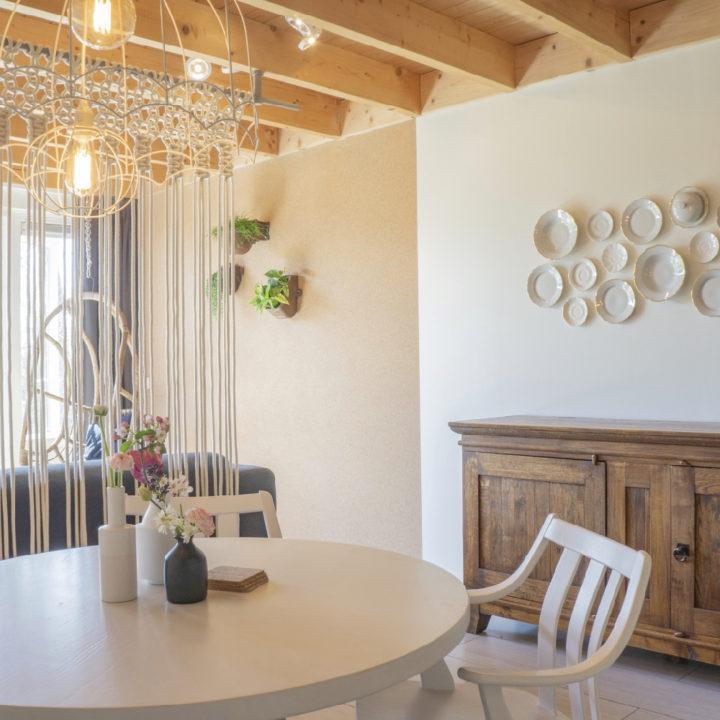 Appartement met bordjes aan de muur, een ronde zithoek en stoere houten balken