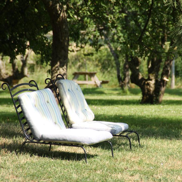 Twee ligstoelen onder de bomen in de tuin van Domaine de Savigny