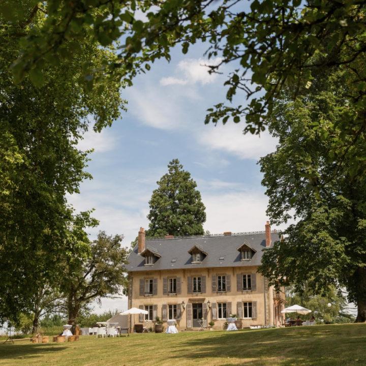Domaine de Savigny tussen de bomen, met witte stoelen voor het huis