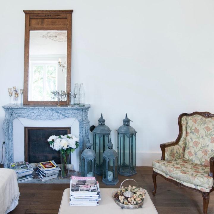 Antieke fauteuil bij een schouw, met lantaarns en een salontafel met stapel tijdschriften