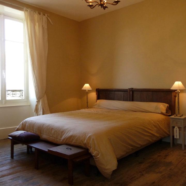 Tweepersoons bed met houten achterwand en schemerlampjes op de nachtkastjes