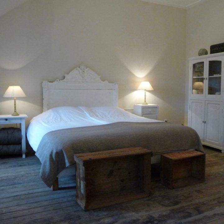 Een B&B kamer met tweepersoons bed, houten kisten naast het bed