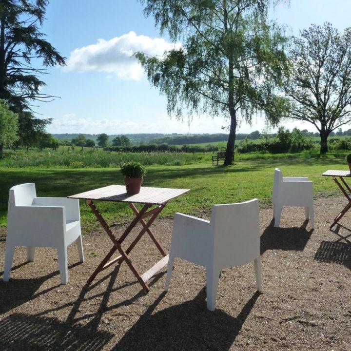 Witte terrasstoelen en een houten tafeltje, groot grasveld