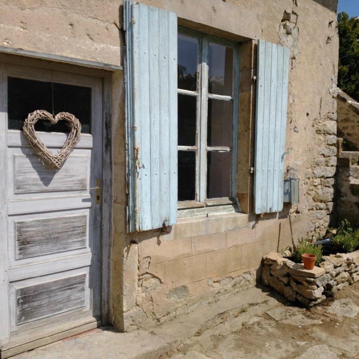 Een oude houten deur in de gite en blauwe luiken
