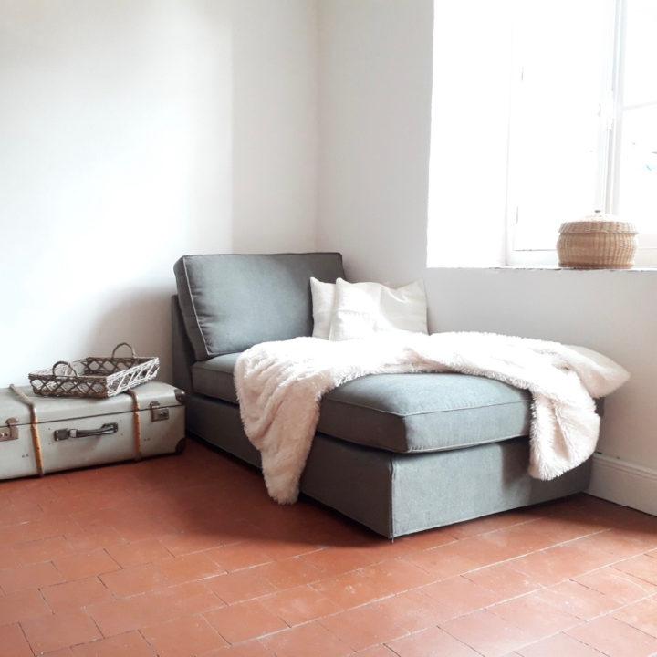 Grijze loungebank in de hoek van een kamer, met witte plaid en kussens erop
