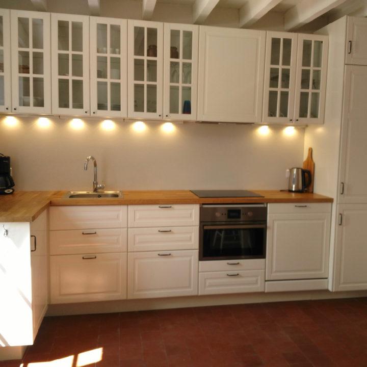Een witte landelijke keuken met houten aanrechtblad