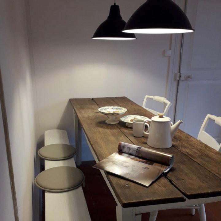 Lange keukentafel met een wit bankje langs de wand en zwarte lampen erboven