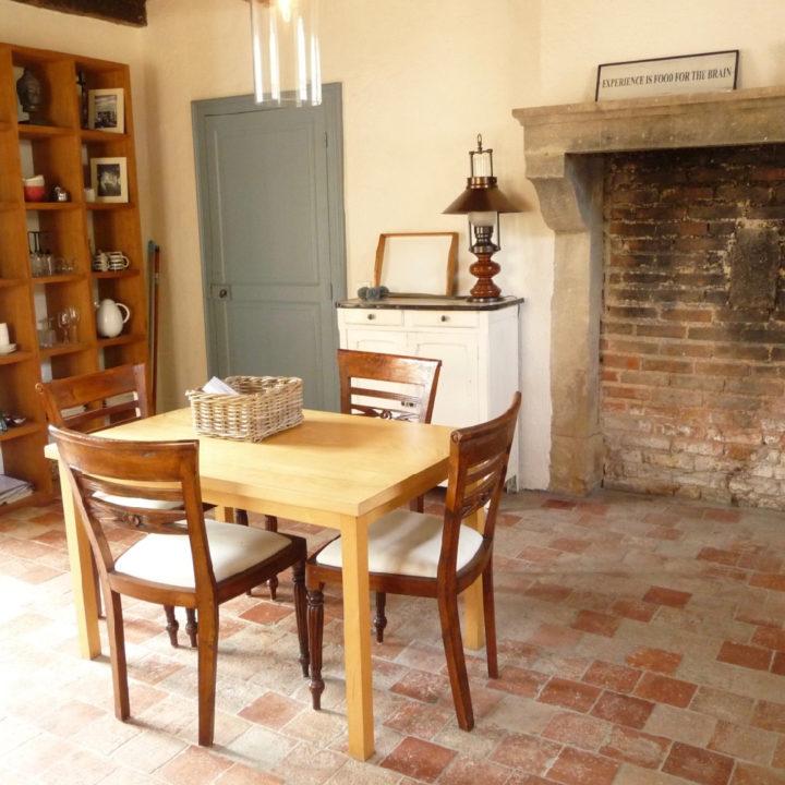 Een eettafel met drie houten stoelen in de keuken van het vakantiehuis, met grote schouw langs de muur