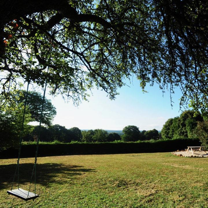 Een grote tuin met groen grasveld, een schommel in de boom en een picknicktafel in de verte