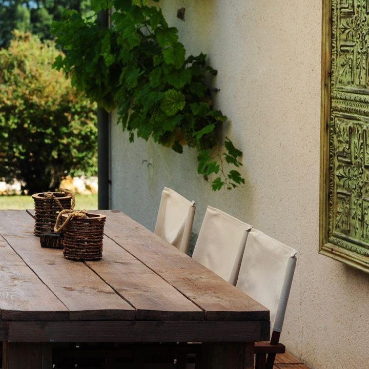 Close up van de eettafel op het terras met een kant drie regisseurstoelen