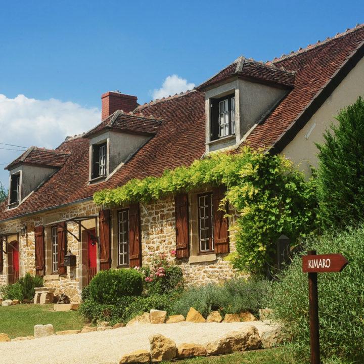 Een typisch Franse boerderij met luiken en een wegwijzer met de tekst Kimaro
