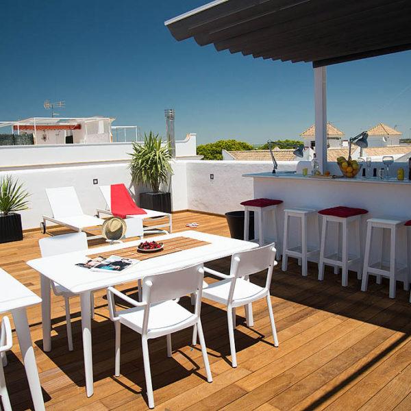 Roof terrace met witte stoelen en rode accessoires