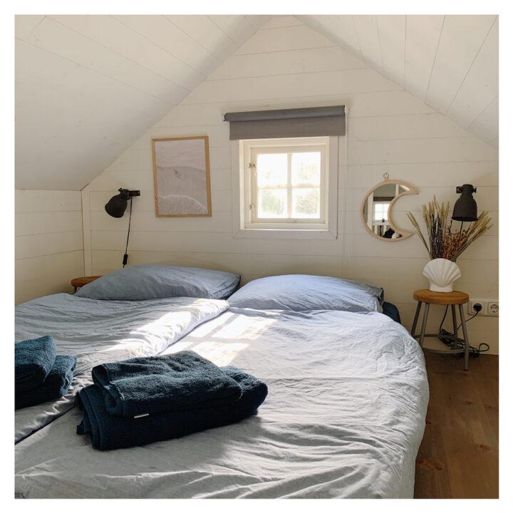De slaapkamer op de vide heeft een tweepersoons bed met boxspring.