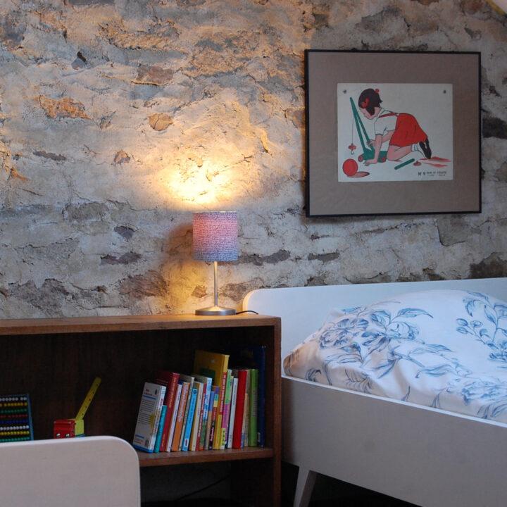 Kinderkamer met twee kinderbedden en een kastje met boeken