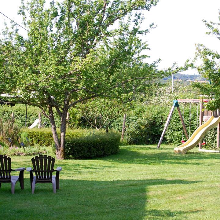 Omheinde tuin met speeltoestellen en lekkere zitjes