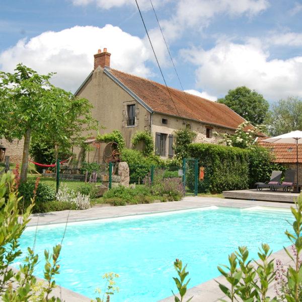 Zwembad met ligstoelen, parasols en Franse boerderij ernaast