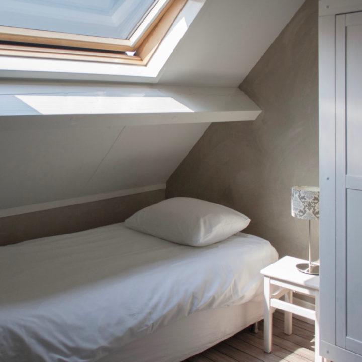 Bed onder schuin dak met Velux dakraam