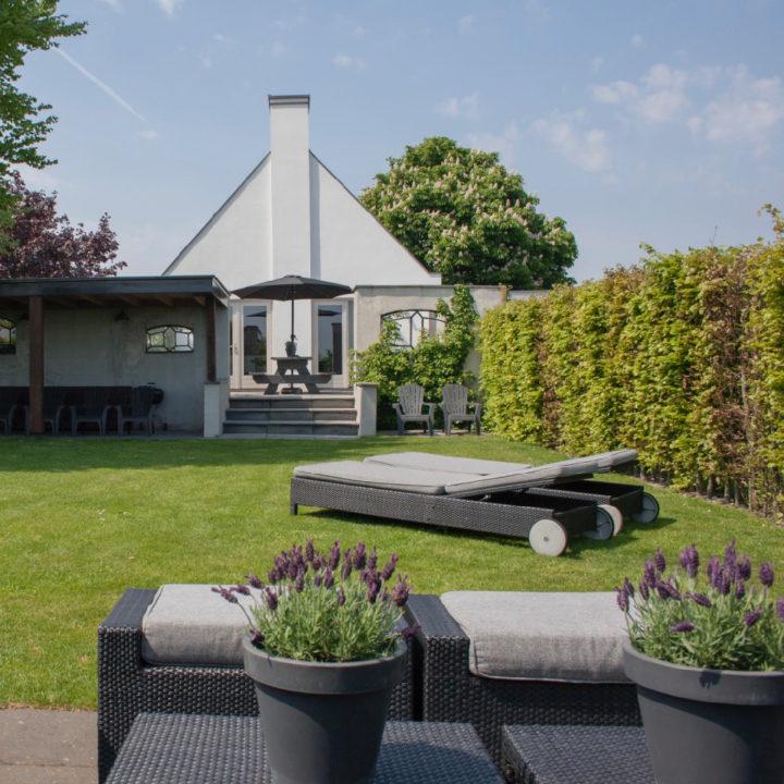 Ligstoelen in achtertuin op gras bij wit vakantiehuis