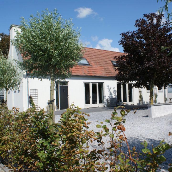 Wit vakantiehuis met grote openslaande deuren en oranje pannendak