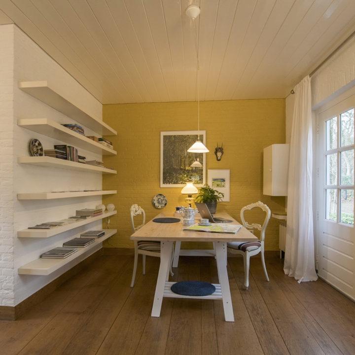 Eethoek met witte tafel en stoelen, een witte muur met witte schappen en een okergele achterwand.